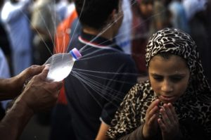 An Egyptian young girl reacts as she is sprayed water on her face during a rally of supporters of deposed president Mohamed Morsi outside Rabaa al-Adawiya mosque on July 15, 2013 in Cairo, Egypt. A top US official pressed Egypt's interim leaders for a return to elected government after the army ousted Morsi, whose supporters massed to rally for his return. AFP PHOTO/GIANLUIGI GUERCIA