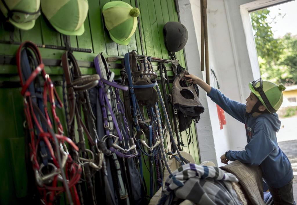 Varga Mátyás, az Alagi Zsokéiskola tanulója a lószerszámoknál az Alagi Versenyló Tréningközpontban Dunakeszin. MTI Fotó: Mohai Balázs