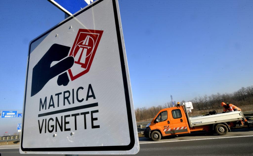 A Magyar Közút Nonprofit Zrt. munkatársai helyeznek ki egy a fizetõs autópálya-szakaszt jelzõ táblát az M0-ás autóúton, az M3-as autópálya lehajtójának közelében 2014. december 31-én. MTI Fotó: Máthé Zoltán